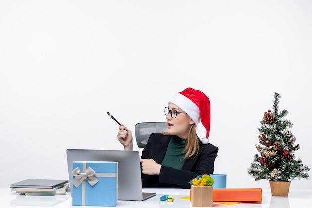Donna bionda con un cappello di babbo natale seduto a un tavolo con un albero di natale e un regalo