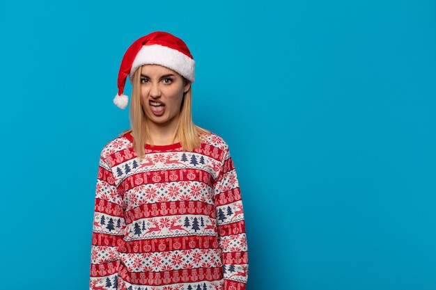 サンタの帽子をかぶった金髪の女性は、嫌悪感とイライラを感じ、舌を突き出し、厄介で厄介なものを嫌います