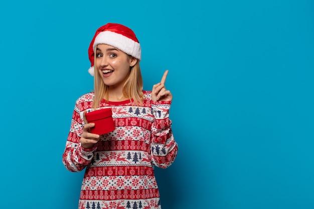 Блондинка в новогодней шапке почувствовала себя счастливым и взволнованным гением, реализовав идею, весело подняв палец, эврика!