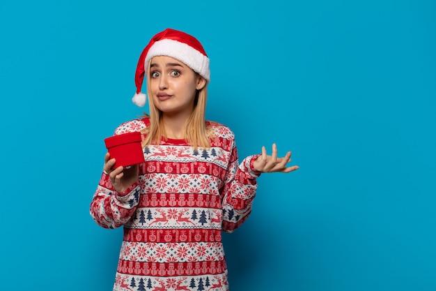サンタの帽子をかぶった金髪の女性は、困惑して混乱し、疑って、重みを付けたり、面白い表現でさまざまなオプションを選択したりします
