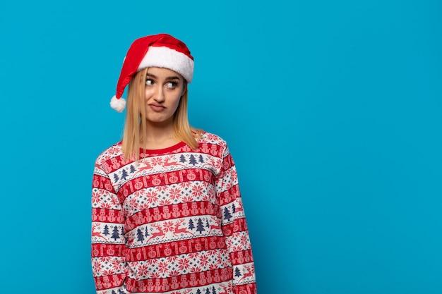 산타 모자와 금발의 여자는 슬프고, 화가 나거나 화가 나서 부정적인 태도로 측면을 찾고, 불일치에 찌푸린