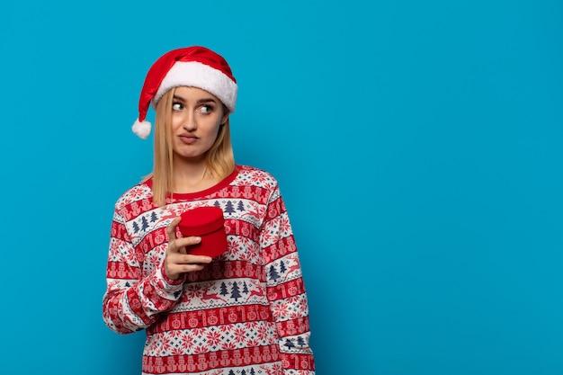 산타 모자를 쓴 금발의 여인은 슬프고 화 나거나 화가 나고 부정적인 태도로 측면을 찾고 불일치에 찌푸린
