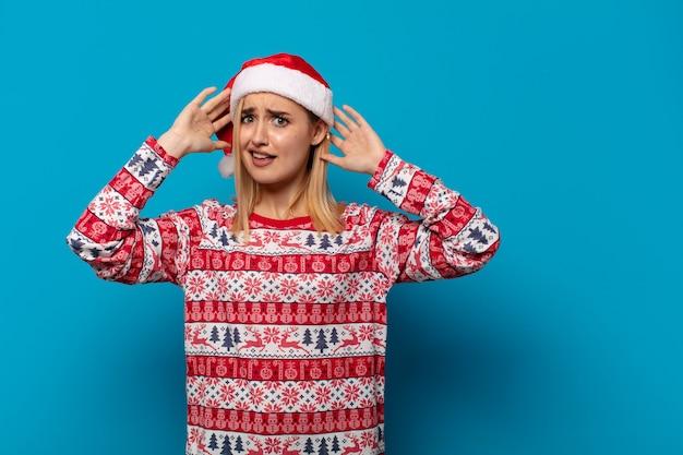 サンタの帽子をかぶった金髪の女性が、ストレス、心配、不安、恐怖を感じ、手を頭に当て、間違えてパニックに陥る