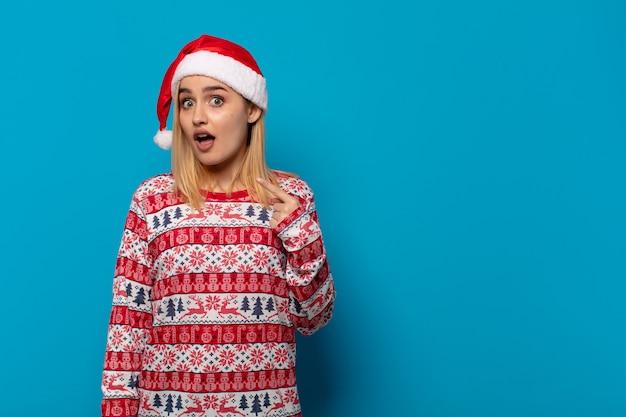충격과 입 벌리고 놀란 산타 모자와 금발의 여자는 자기를 가리키는