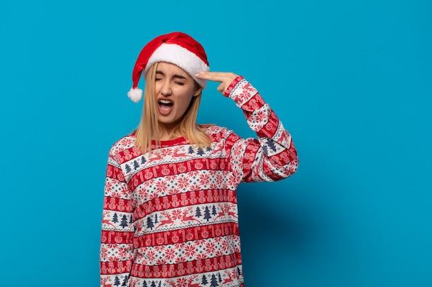 불행 하 고 스트레스를 찾고 산타 모자와 금발 여자, 머리를 가리키는 손으로 총 기호를 만드는 자살 제스처