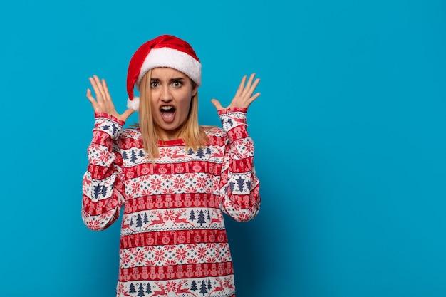 산타 모자와 함께 금발의 여인이 공중에서 손으로 비명을 지르고 분노하고 좌절감을 느끼고 스트레스를 받고 화가납니다.