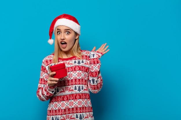 サンタ帽子をかぶった金髪の女性が両手を上げて叫び、怒り、欲求不満、ストレス、動揺を感じている
