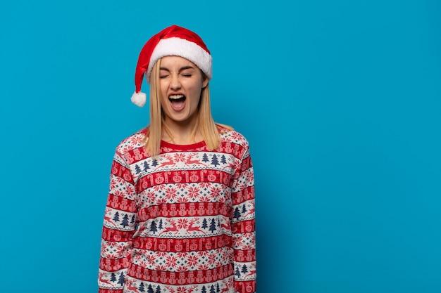 산타 모자가 적극적으로 외치고, 매우 화가 나고, 좌절하고, 분노하거나 짜증이 나서, 비명을 지르는 금발의 여인