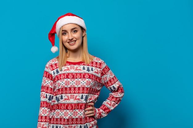 サンタ帽子をかぶった金髪の女性が、腰に手を当てて楽しそうに微笑み、自信に満ち、ポジティブで、誇り高く、友好的な態度