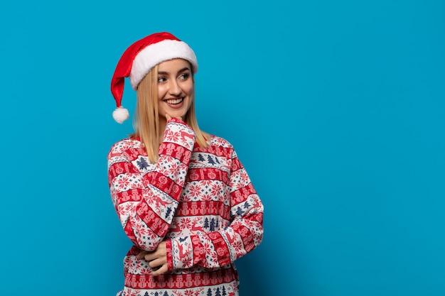 サンタの帽子をかぶったブロンドの女性は、あごに手を添えて幸せで自信に満ちた表情で笑って、不思議に思って横を向いています