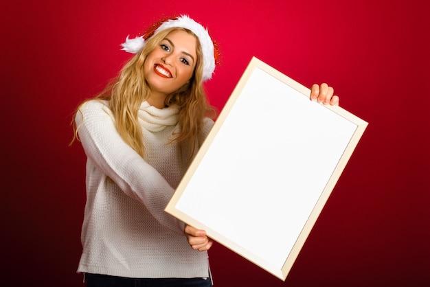 빈 보드를 들고 산타의 모자와 금발 여자