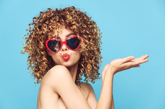 Blonde woman with sunglasses posing on blue