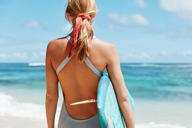 Blonde woman with surfboard on beach