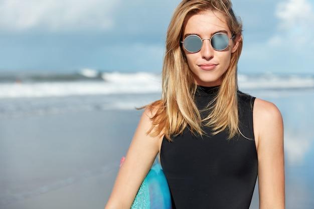 ビーチでサーフボードを持つブロンドの女性