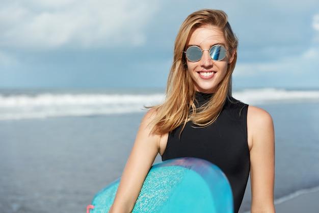 Блондинка с доской для серфинга на пляже