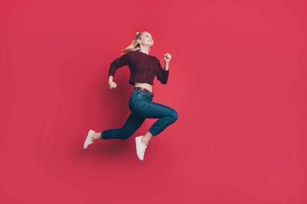 Блондинка с топ-узлами позирует и прыгает против красной стены