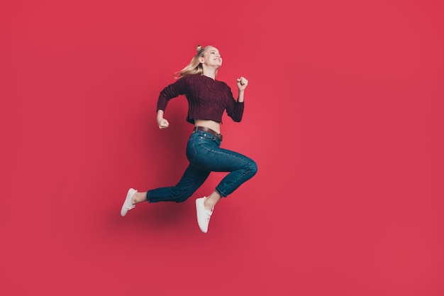 Blonde woman with top-knots posing and jumping against the red wall