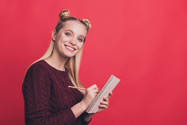 赤い壁にノートでポーズをとってトップノットを持つブロンドの女性