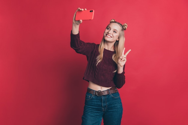 Blonde woman with top-knots posing with her phone against the red wall
