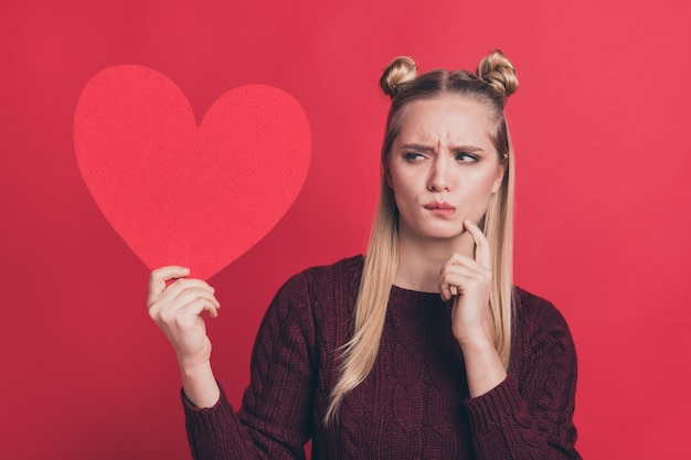 Blonde woman with top-knots posing with red paper heart against the red wall