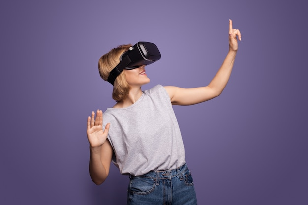 Blonde woman with vr headset is touching something while posing on a violet wall