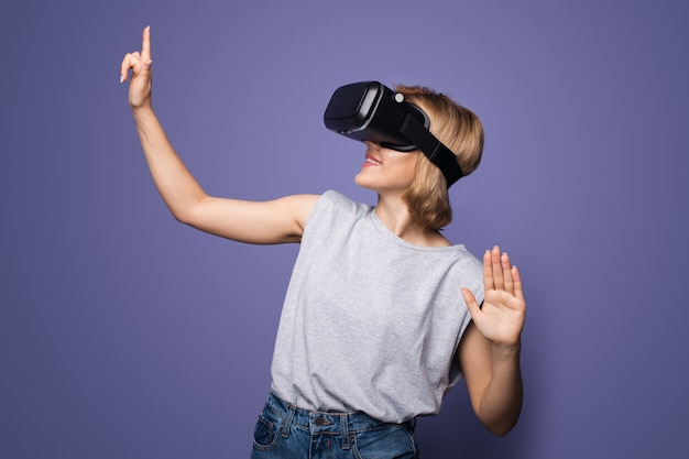Blonde woman with vr headset touching something on a violet  wall