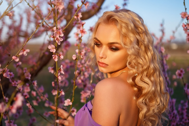 Blonde woman with wavy hair posing with blooming peach trees against the sky