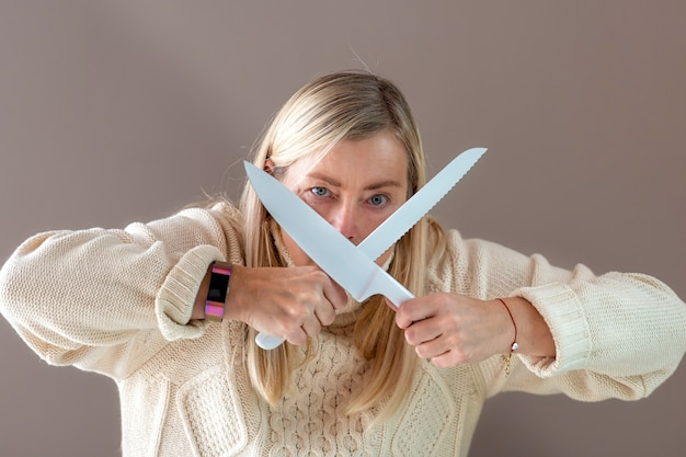Blonde woman with white knives in hands