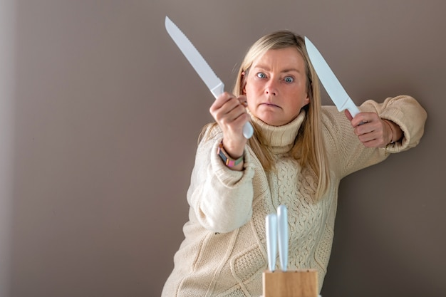 手に白いナイフを持つブロンドの女性