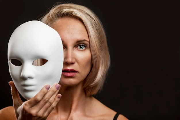 Blonde woman with a white mask in her hand. close-up. black background.
