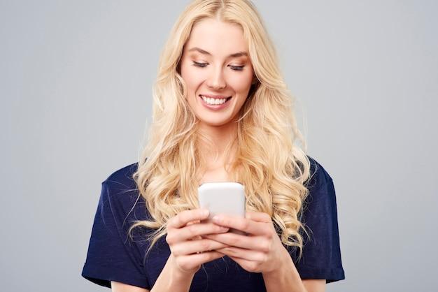 白いスマートフォンを持つブロンドの女性