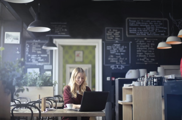Blonde woman working from a coffee shop