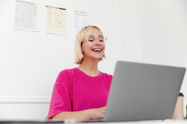 그녀의 노트북에 집에서 일하는 금발의 여자