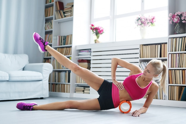 Blonde woman workout exercises with foam roller