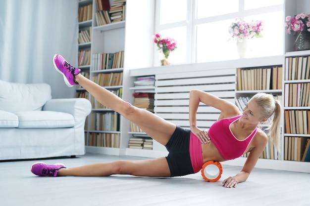 Esercizi di allenamento donna bionda con rullo di schiuma