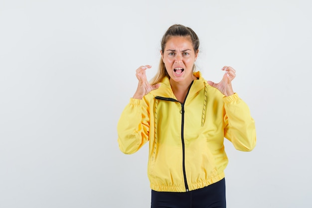 Blonde woman in yellow bomber jacket and black pants raising hands in angry manner and looking harried