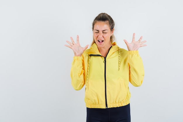 Blonde woman in yellow bomber jacket and black pants raising hands as showing restriction gesture and screaming and looking annoyed