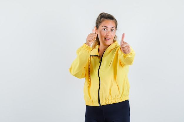 Blonde woman in yellow bomber jacket and black pants showing double thumbs up and looking happy