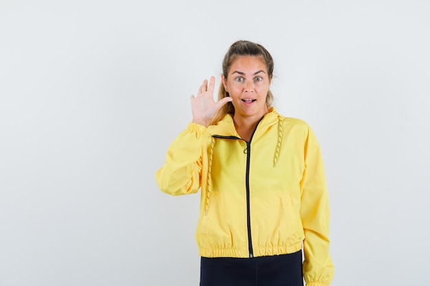 Donna bionda in bomber giallo e pantaloni neri che mostra il segnale di stop e che sembra felice