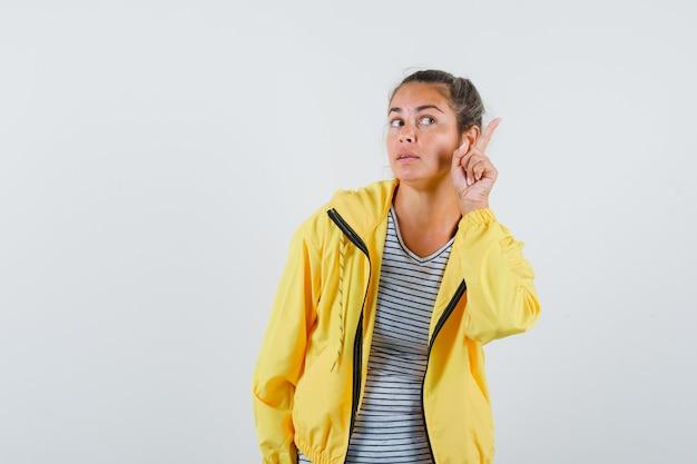 Donna bionda in bomber giallo e camicia a righe alzando il dito indice in gesto di eureka, distogliendo lo sguardo e guardando pensieroso