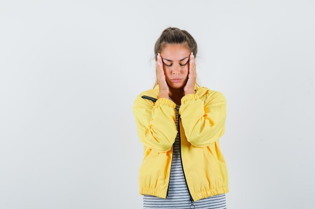 Blonde woman in yellow bomber jacket and striped shirt rubbing temples and closing eyes and looking serious