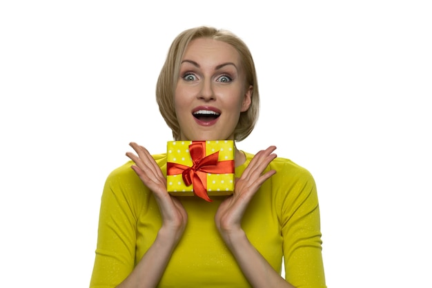 Blonde woman in yellow turtleneck presses the gift to the chest and looking at camera with widely open eyes. on valentine's day lovers day. Premium Photo