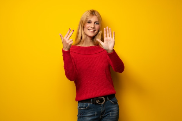 Blonde woman over yellow wall counting eight with fingers