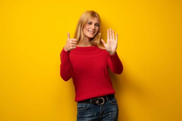 Blonde woman over yellow wall counting six with fingers