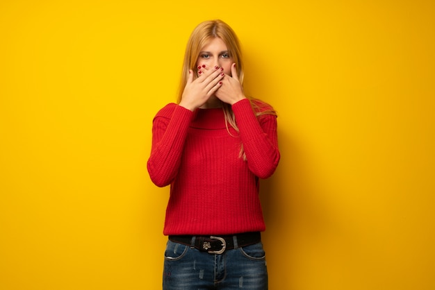 Blonde woman over yellow wall covering mouth with hands for saying something inappropriate