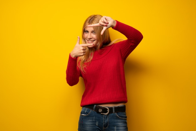 Blonde woman over yellow wall focusing face. framing symbol