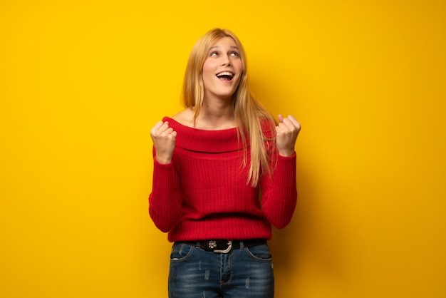 Blonde woman over yellow wall frustrated by a bad situation