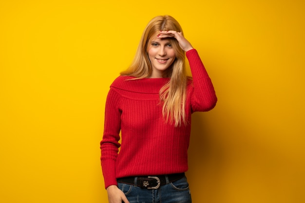Blonde woman over yellow wall looking far away with hand to look something