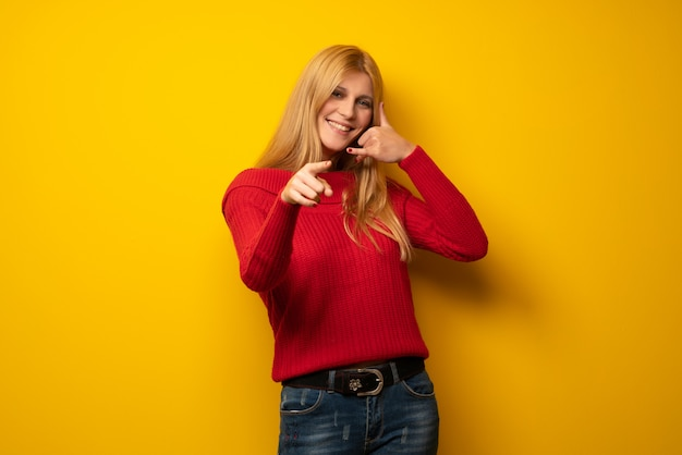 Blonde woman over yellow wall making phone gesture and pointing front