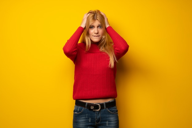 Blonde woman over yellow wall takes hands on head because has migraine